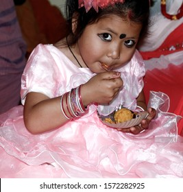 cute baby girl eating sweet and her beautiful look from Nepal, model