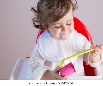 Cute baby girl eating yogurt smiling. Her pretty face has yogurt around her mouth.