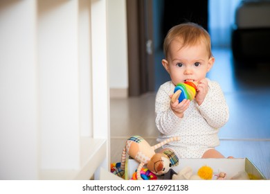 cute baby girl gnawing a wooden colorful toy