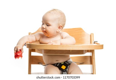 Cute baby girl going to drop tomato while sitting in high chair over white background