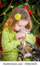 Cute baby girl in green dress is kissing a cat near christmas tree