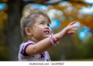 Cute baby girl is having fun in the autumn forest