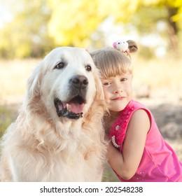Cute baby girl holding labrador outdoors