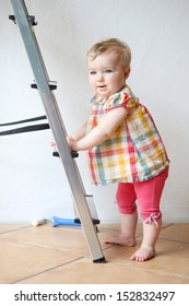 Cute baby girl holding a step ladder in domestic room during repair works