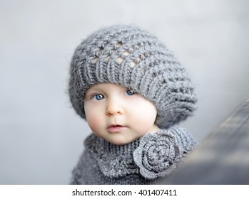 cute baby girl in knitted beret is looking to the camera