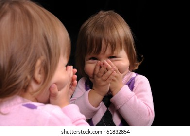 Cute baby girl looking at the mirror and laughing