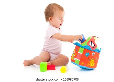 Cute baby girl lost in playing with toys, wearing bodysuit.