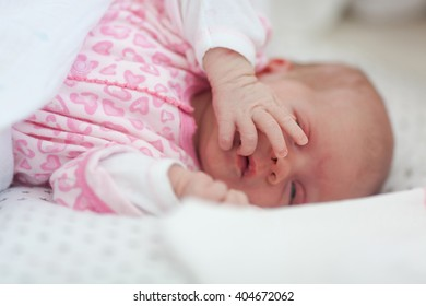 Cute baby girl lying in bed and covering her face with hand.