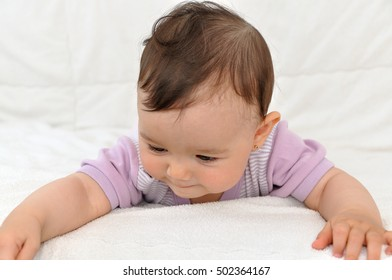 Cute baby girl lying on her stomach in bed and playing