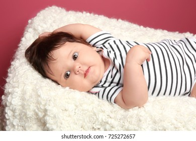 Cute baby girl lying on plaid at home