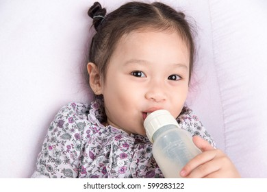 Cute baby girl with a milk bottle on a white blanket