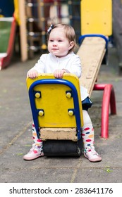 Cute baby girl on a seesaw swing at the playground