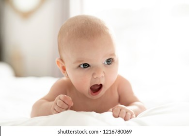 A Cute baby girl on a white bed at home yawn