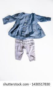Cute baby girl outfit - denim top with ruffles and long sleeves and grey pants with ruffles - flat lay on white