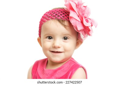 Cute Baby Girl with a Pink Dress and a Big Pink Flower Headband
