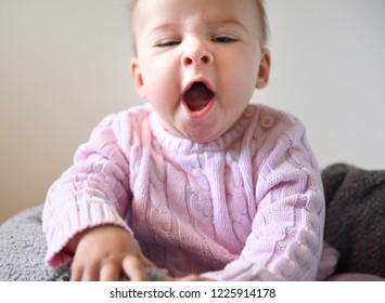 Cute baby girl in pink sweeter yawning