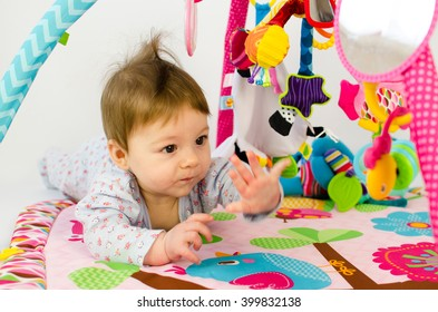 cute baby girl playing in an activity gym