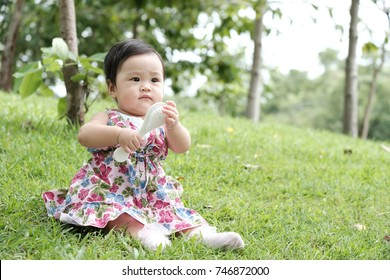 Cute baby girl is playing the comb on her hands