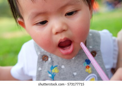 Cute Baby girl playing in the garden, close-up portrait, Portrait of a beautiful baby girl, baby drinking water