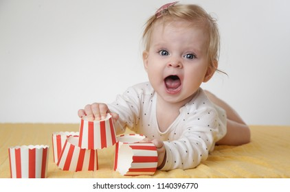 Cute baby girl playing with paper cups