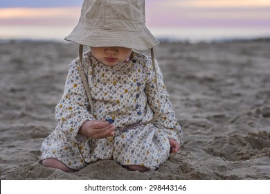 Cute baby girl playing with sea shells on the beach