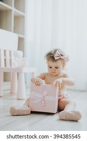 Cute baby girl playing in a white room in the morning