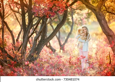 A cute baby girl with a cute puppy is walking in an autumn forest