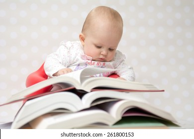 Cute baby girl reading behind a pile of books