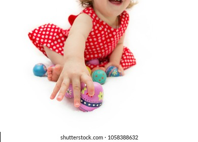 cute baby girl in red dress with painted easter eggs handmade on white isolated background