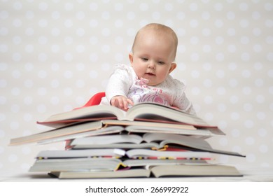 Cute baby girl sitting behind a pile of books