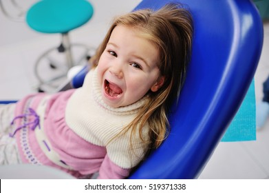 cute baby girl sitting in a dental chair and looking at the camera. caries prevention. little girl screaming in a dental chair. fear of dentist