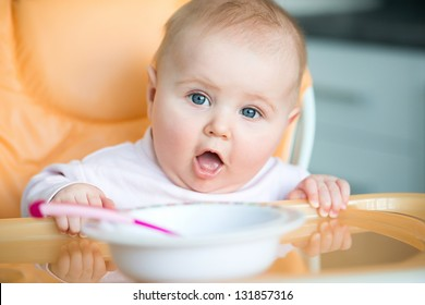 cute baby girl is sitting in her chair and going to eat