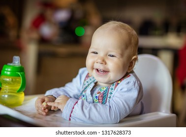 Cute baby girl sitting in high chair and eating piece of bread
