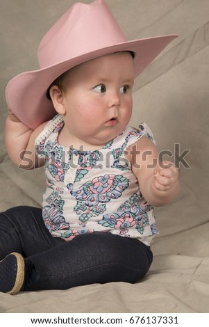 543a3c0a35344 A cute baby girl sitting and looking to the side wearing her pink western  hat.