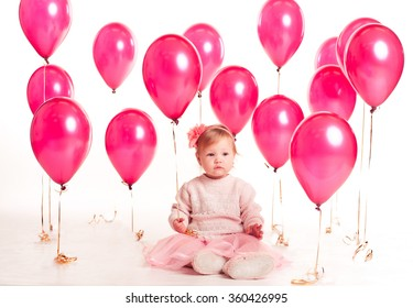 Cute baby girl sitting on floor with pink balloons over white background. Birthday party. Celebration.