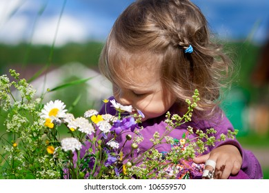 Cute baby girl smells flowers