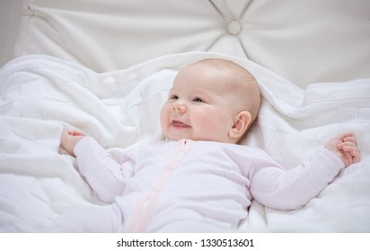 Cute baby girl smiling while lying down on back