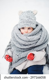 cute baby girl in snowy winter rolled up in oversize grey knitted scarf