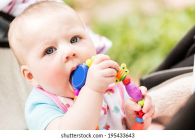 Cute baby girl sucking on her toy.