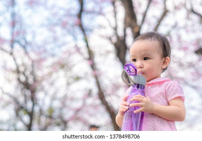 Cute baby girl is sucking water from plastic bottle at summer garden. Background. Copy space. Selective focus.