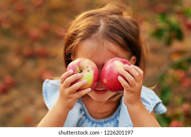 cute baby girl in an summer apple garden