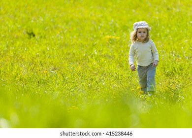 Cute baby girl with sun cap on vivid flower meadow full of yellow flowers.