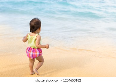 Cute baby girl walking on the beach.