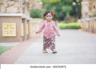 Cute baby girl wearing Baju Kebaya local Malaysian traditional dress at park