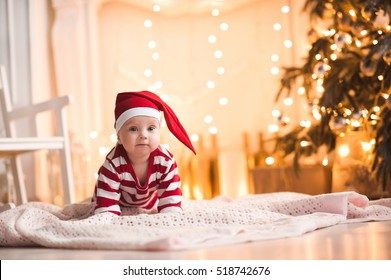 Cute baby girl wearing santa claus suit crawling on floor over Christmas lights. Looking at camera. Holiday season.