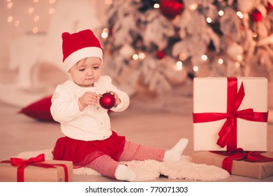 712272dbf Cute baby girl wearing santa hat holding Christmas ball sitting with  presents over Christmas treein room