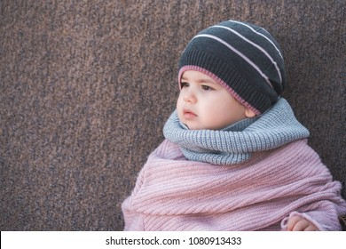 Cute baby girl wearing a warm winter hat and a colorful scarf on a brown background.