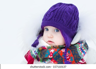 Cute baby girl wearing a warm winter hat and a colorful scarf on a walk in a snowy park