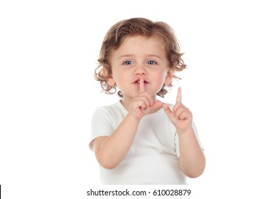 Cute baby has put forefinger to lips as sign of silence, isolated on a white background
