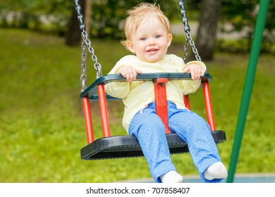Cute baby baby having fun on a swing in a park in autumn